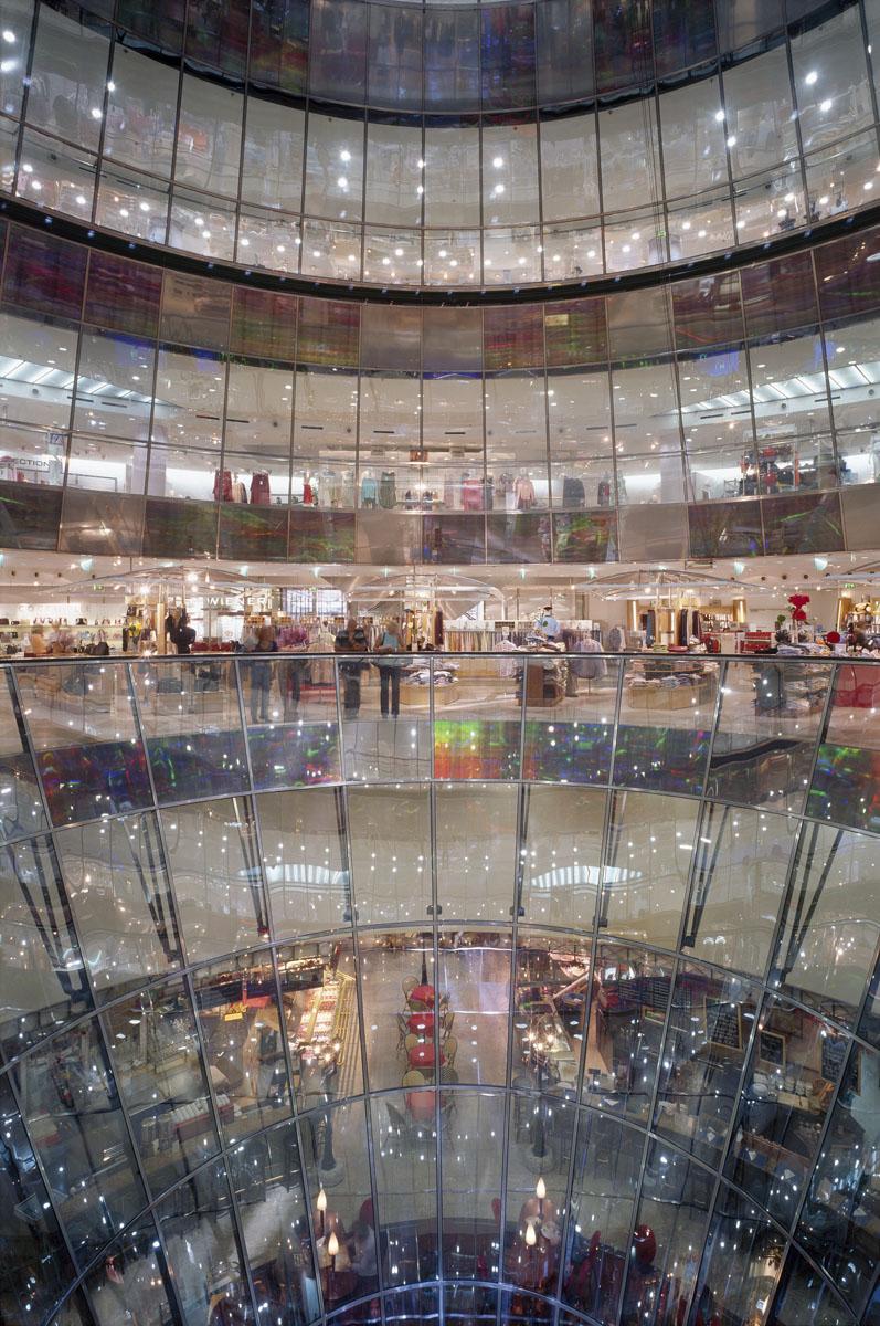 La photographie montre un centre commercial à travers une façade de verre.