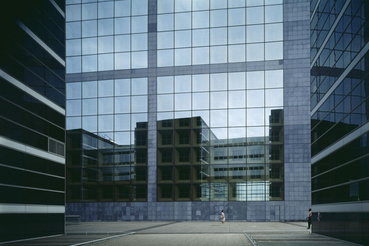 La photographie montre une façade de verre avec deux personnages
