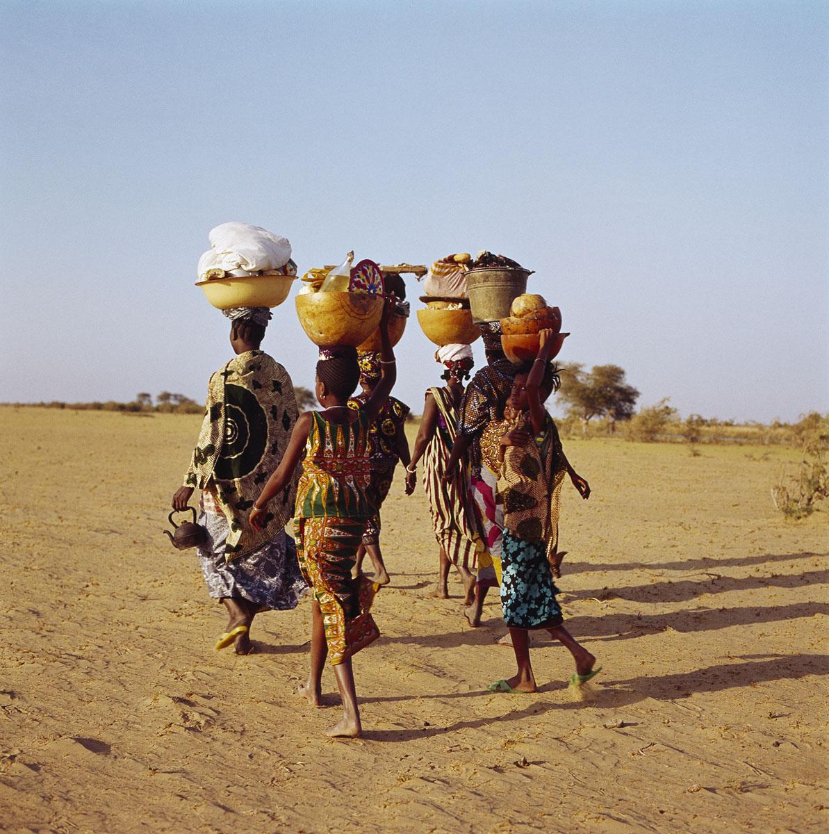La photographie montre quatre femmes marchant dans le sable.