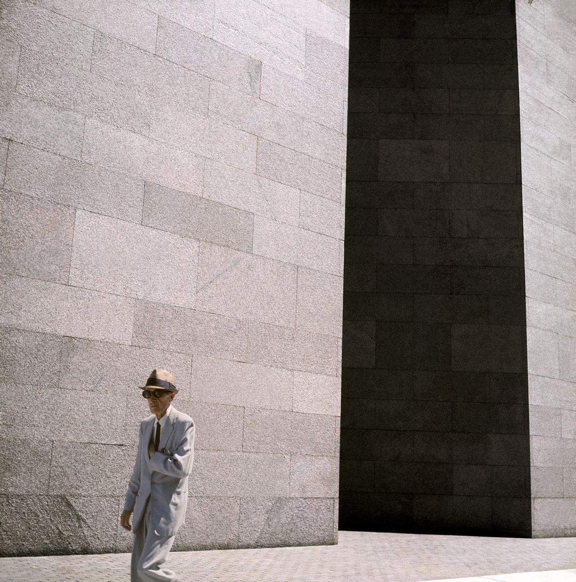La photographie montre un homme chapeauté marchant devant un immeuble.