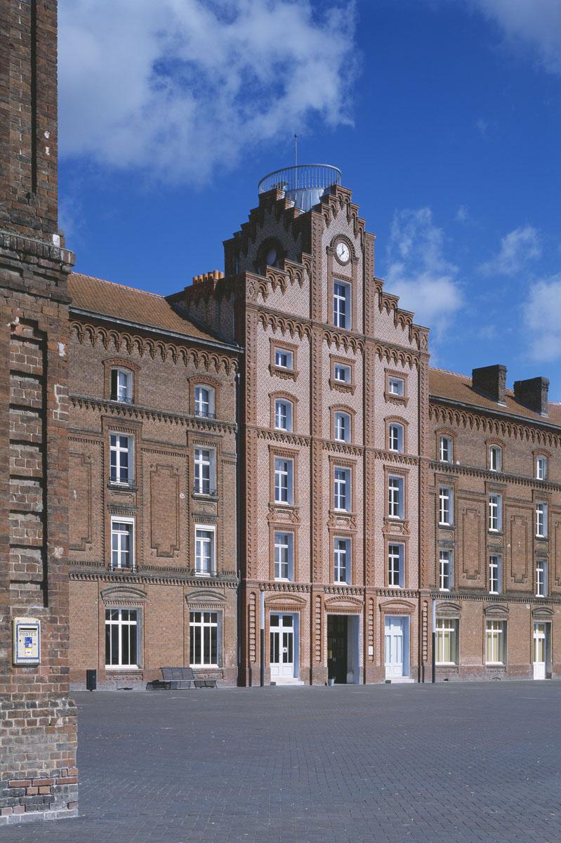 La photographie montre une boîte aux lettres au premier plan du Palais social.