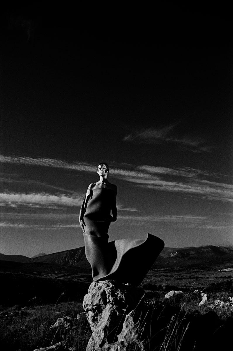 La photographie montre un modèle masqué juché sur un rocher.