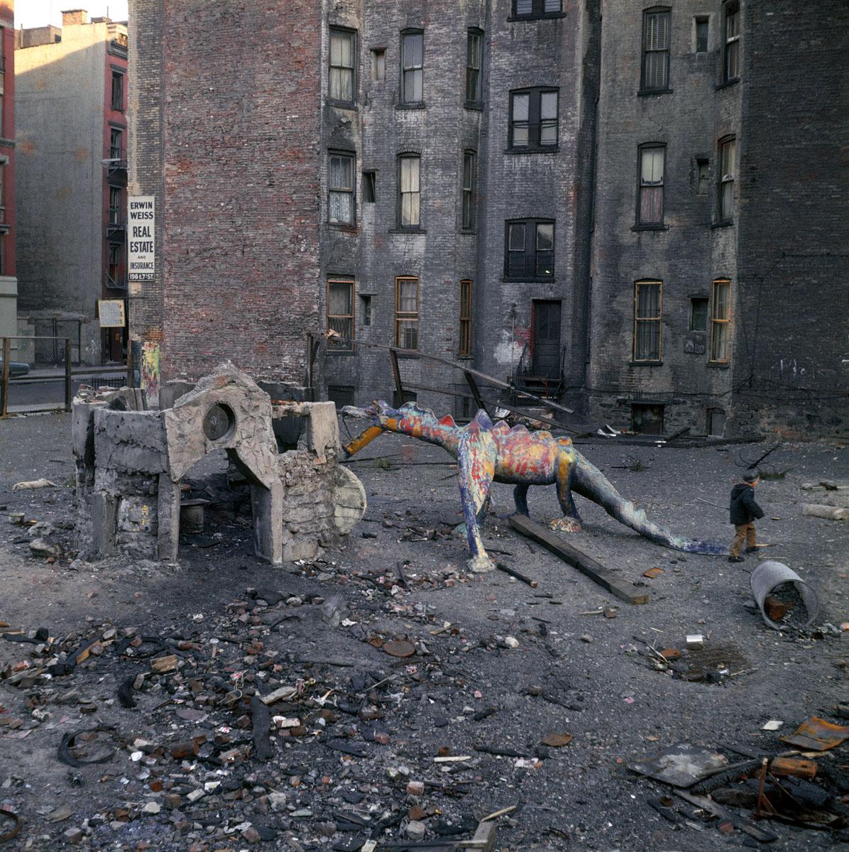 La photographie montre une zone urbaine abandonnée ornée de la sculpture d'un dr