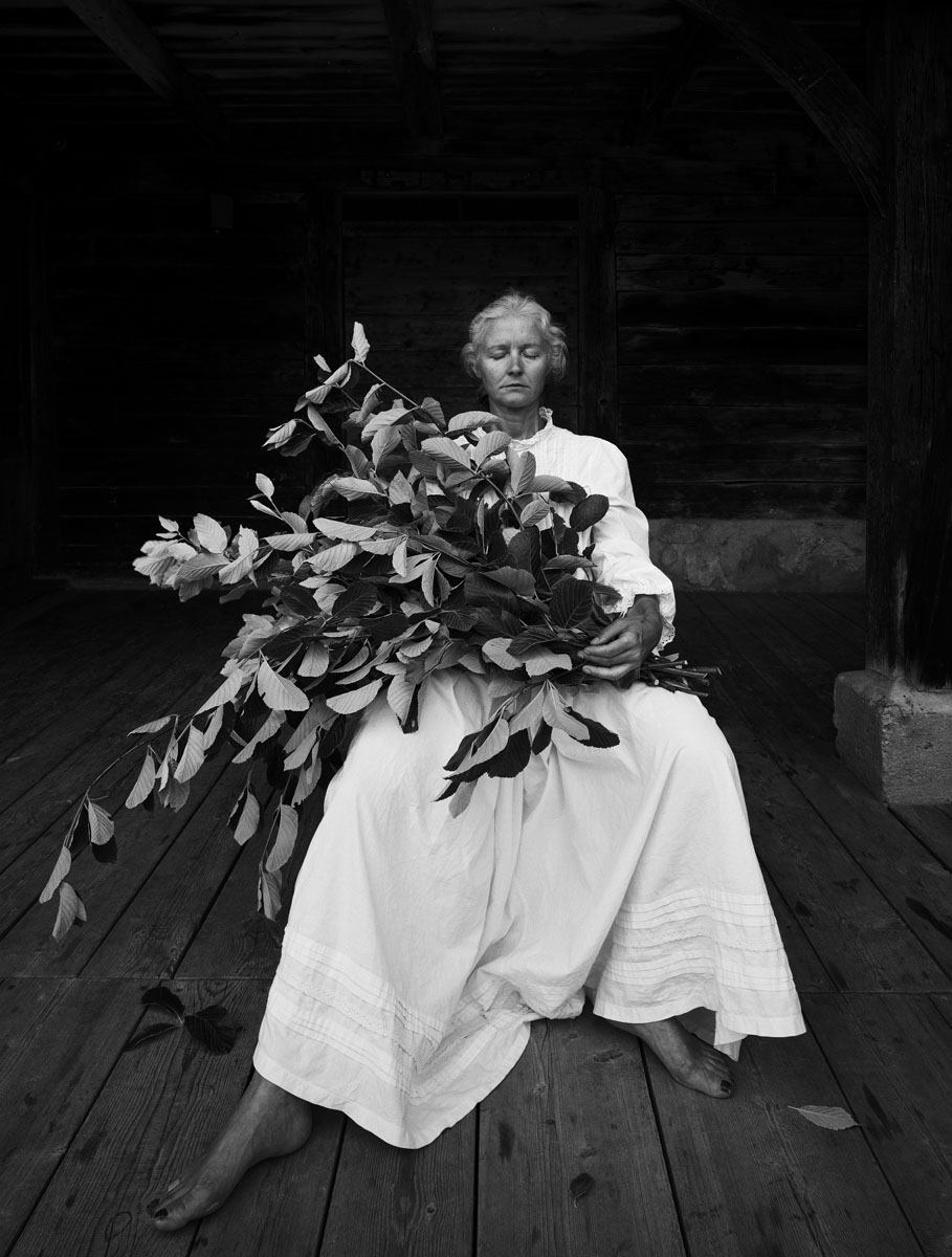 La photographie montre une femme assise en robe blanche, un bouquet de feuilles
