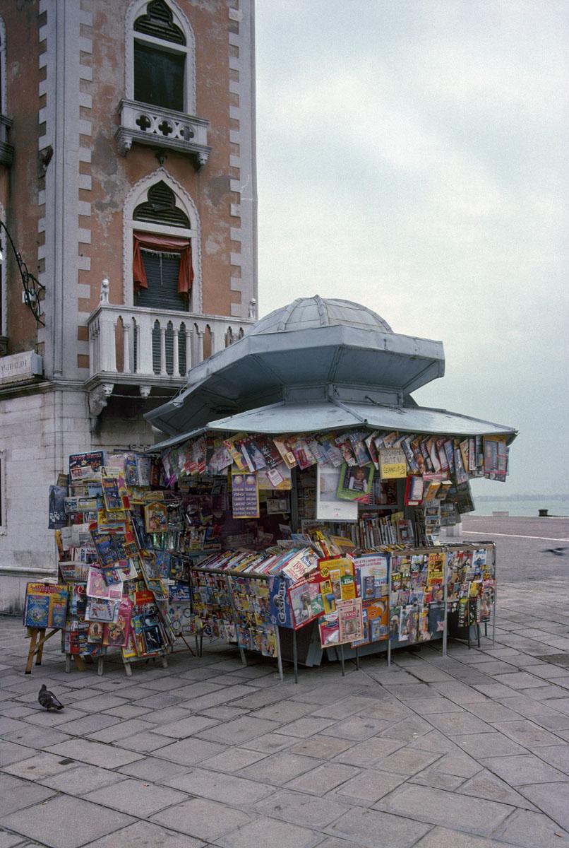 La photographie montre un kiosque à journaux surchargé.