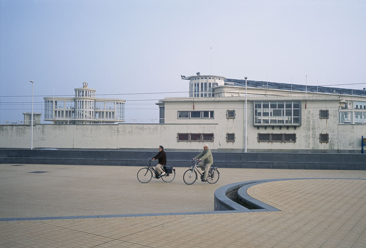 La photographie montre un couple en vélo sur un quai du port d'Ostende.