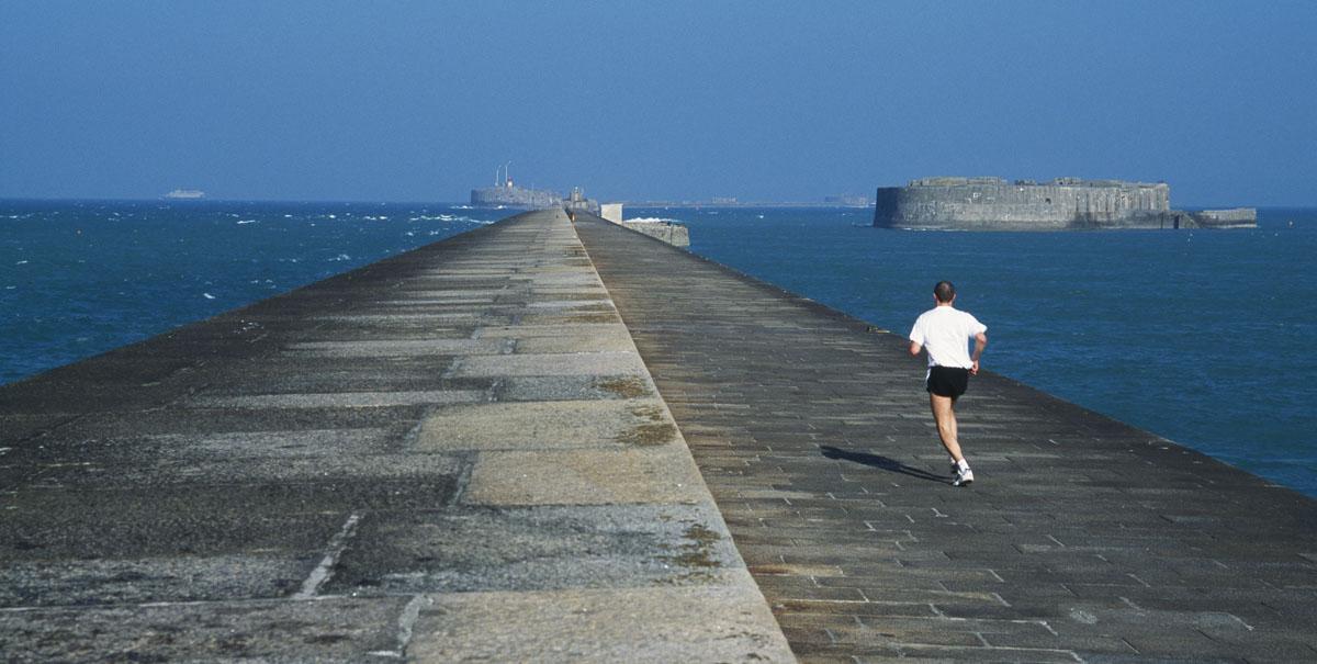 La photographie montre un homme courant en direction de la mer sur une jetée.