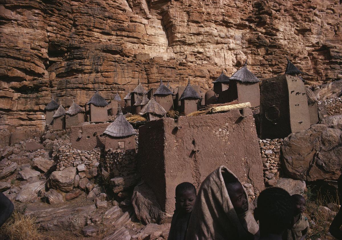 La photographie montre un village de maisons en terre au pied d'(une falaise.