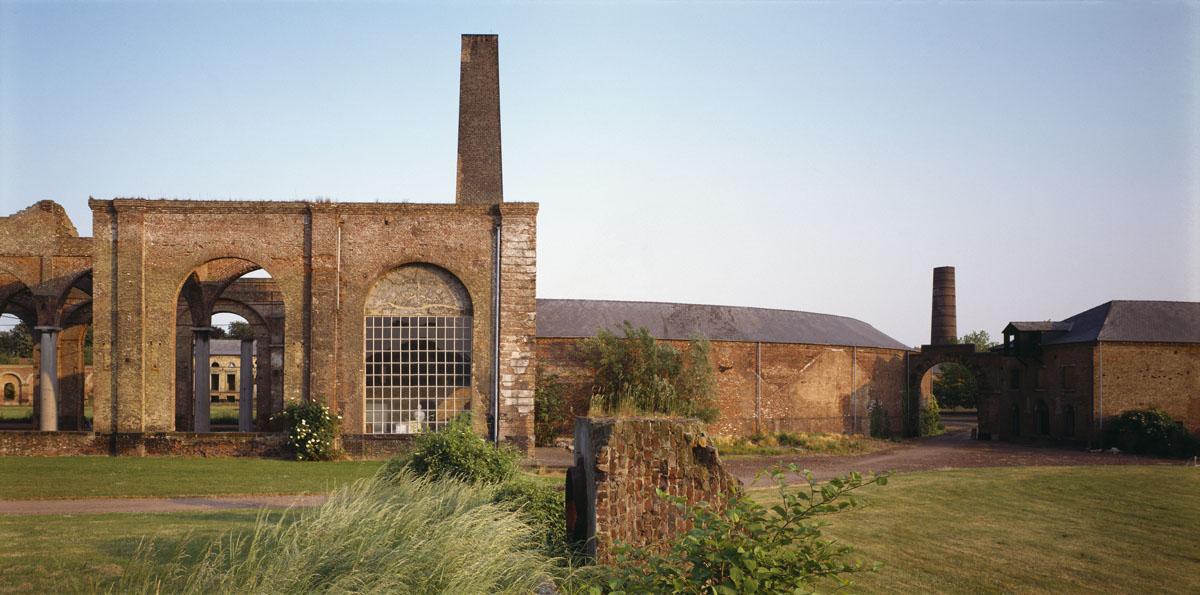 La photographie montre  un ensemble de bâtiments en briques ruinés.
