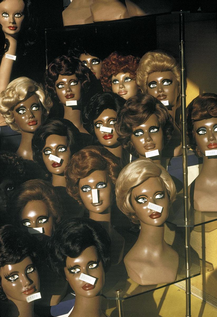 La photographie montre des têtes de mannequin féminins dans une vitrine.