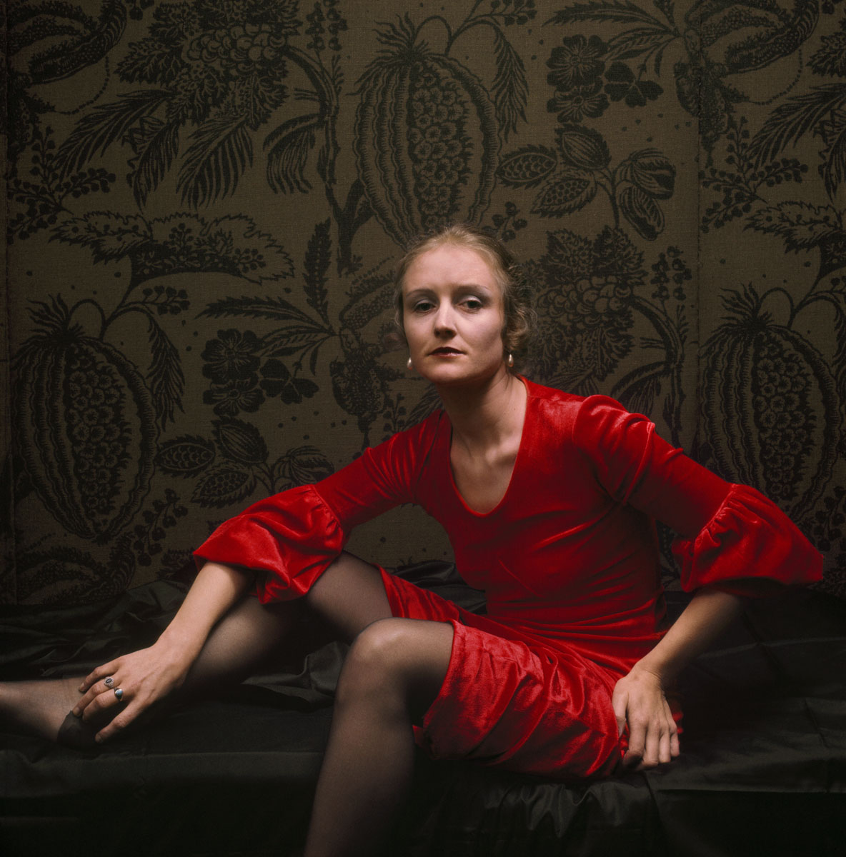 La photographie montre une femme habillée en rouge dans un intérieur.