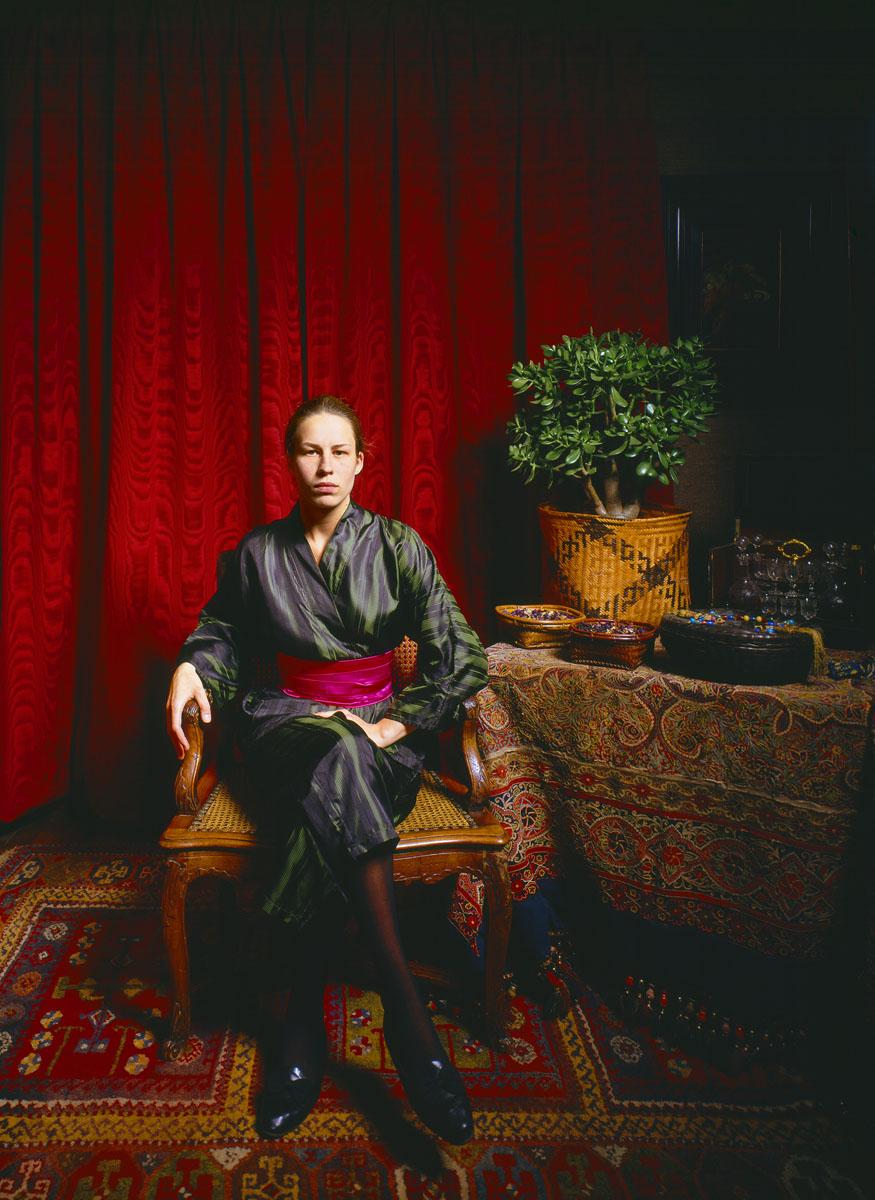 La photographie montre une jeune femme assise dans un intérieur.