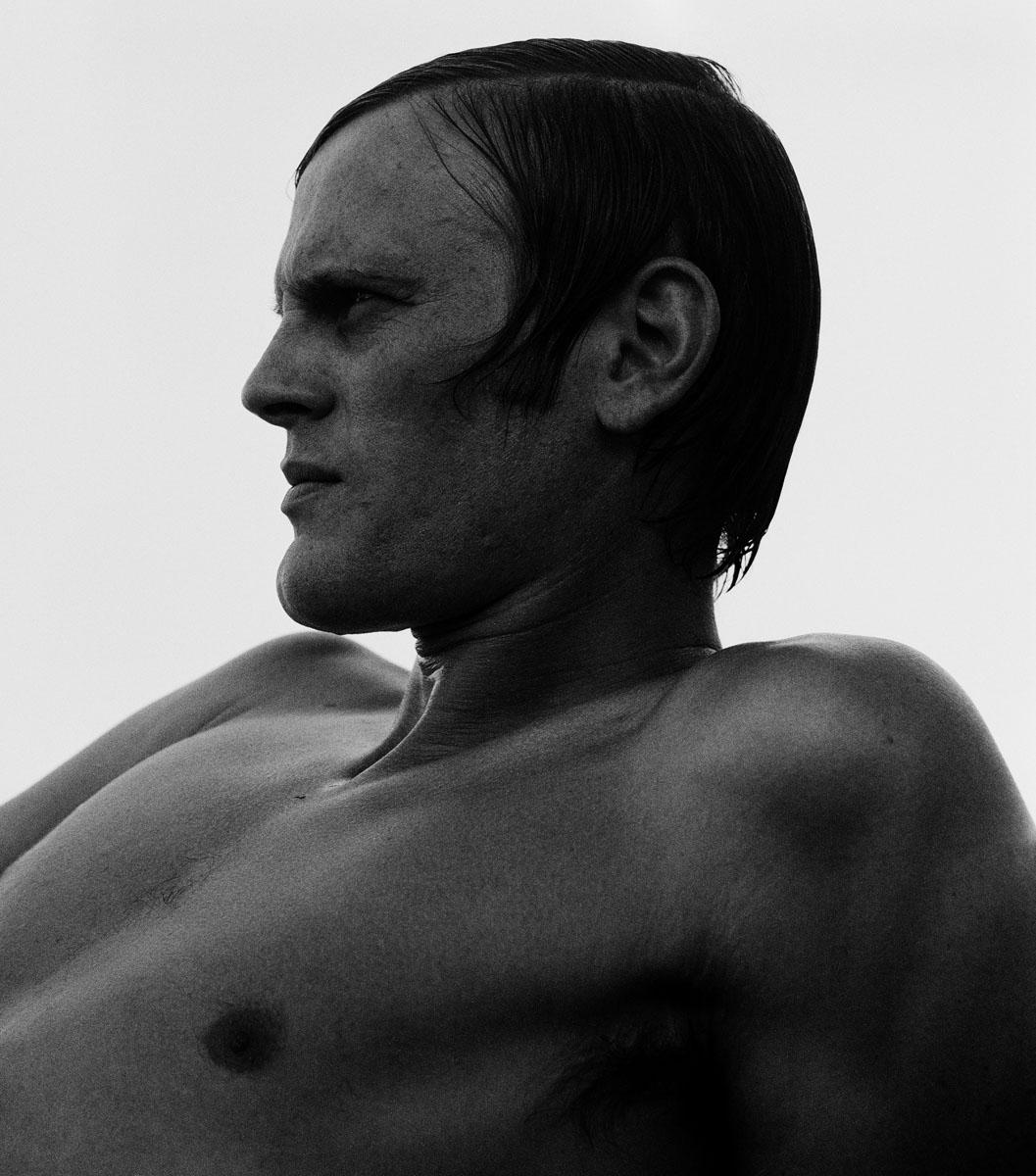 La photographie montre un homme à mi-corps vu de profil.