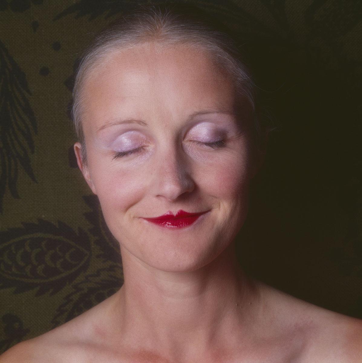 La photographie montre la tête d'une femme souriant les yeux fermés.