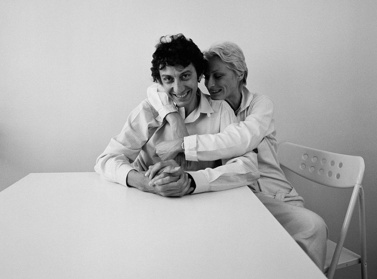 La photographie montre un couple enlacé vêtus de blanc assis à une table.