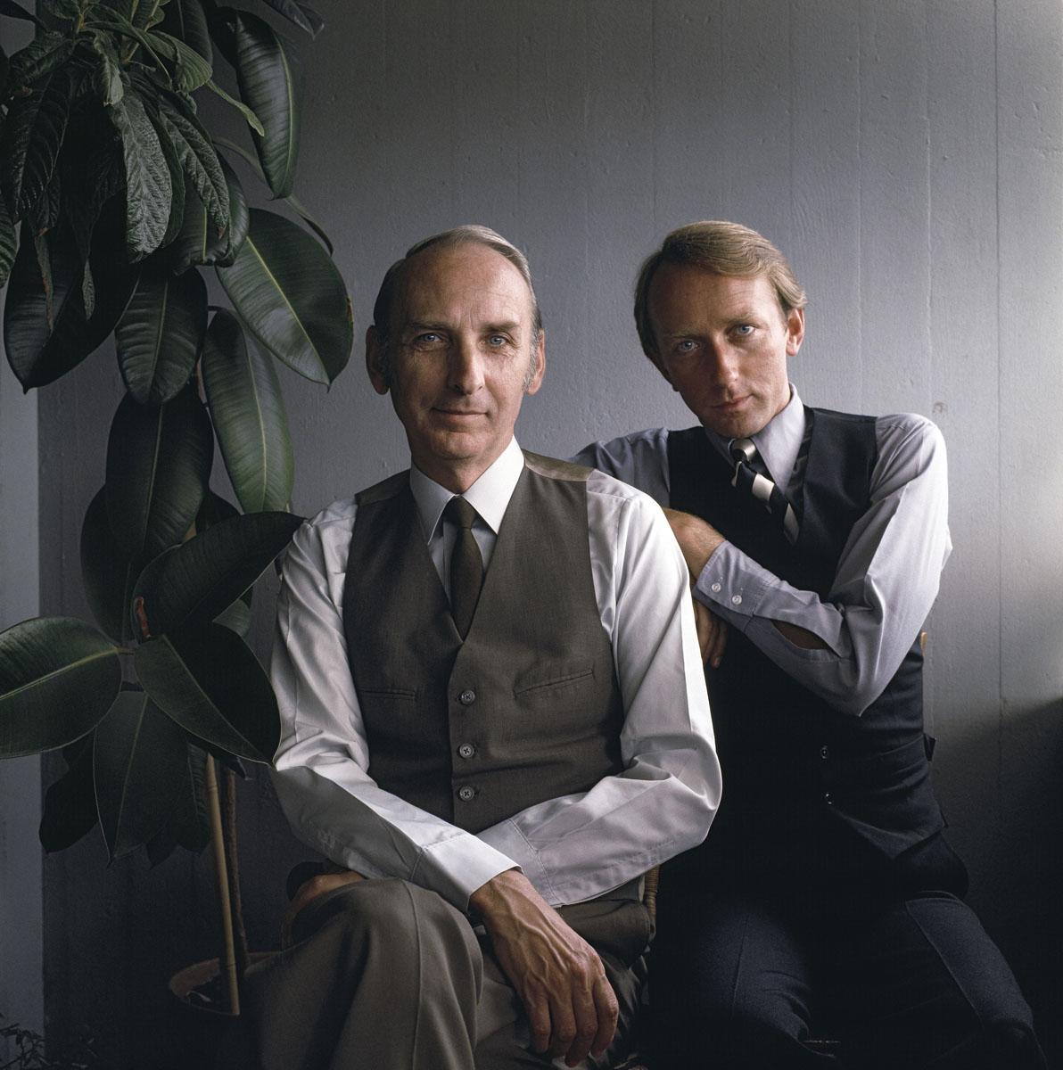 La photographie montre deux hommes à mi-corps, habillés de la même façon, assis