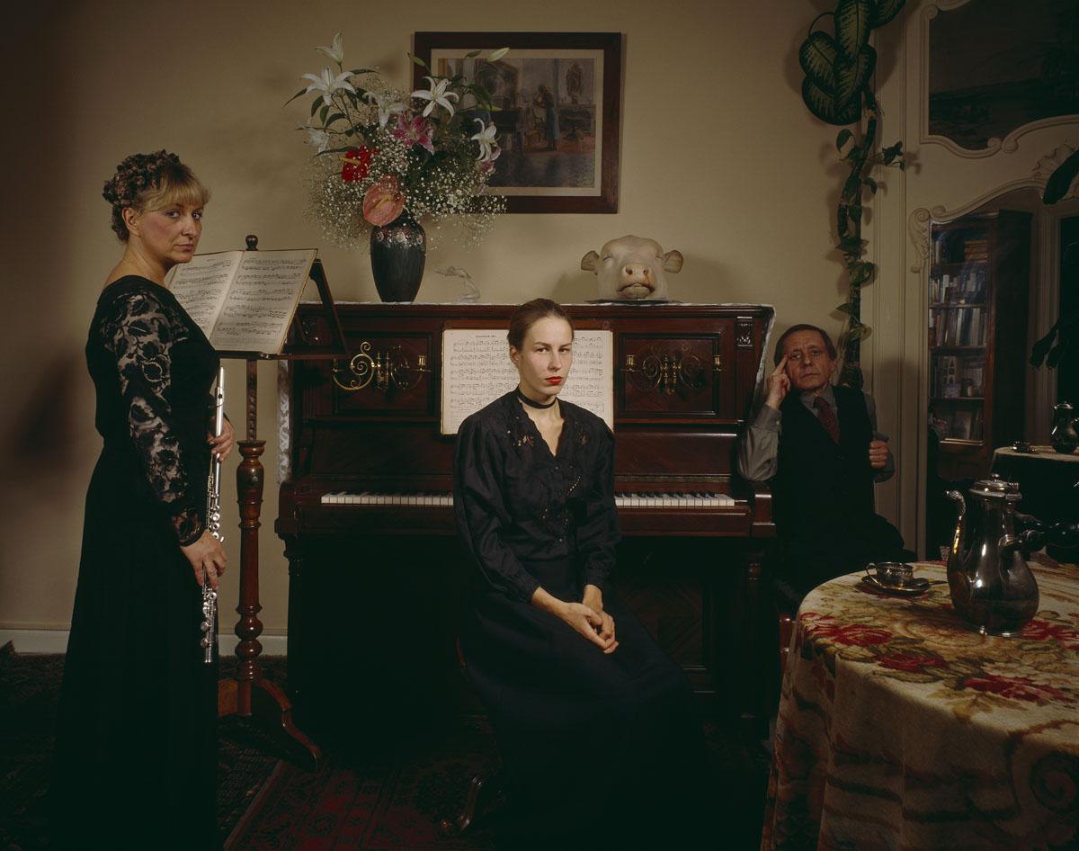 La photographie montre trois personnages dans un intérieur