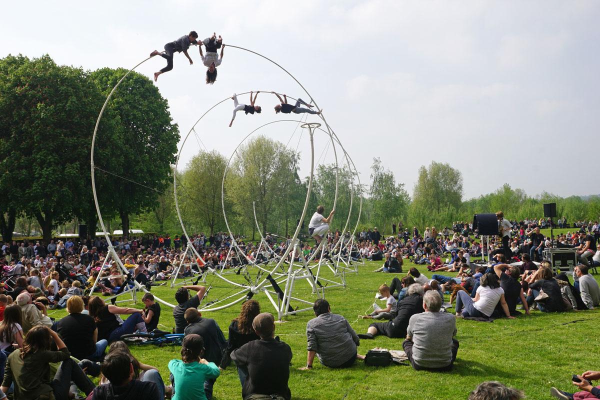 Acrobates sur une structure en spirale dans les jardins du Familistère avec publ