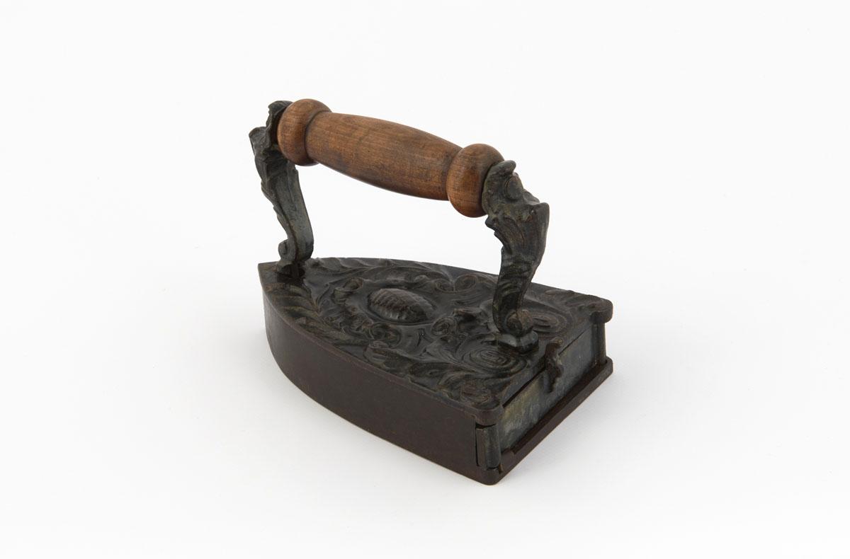 La photographie montre le décor du fer à repasser, placé en position verticale.