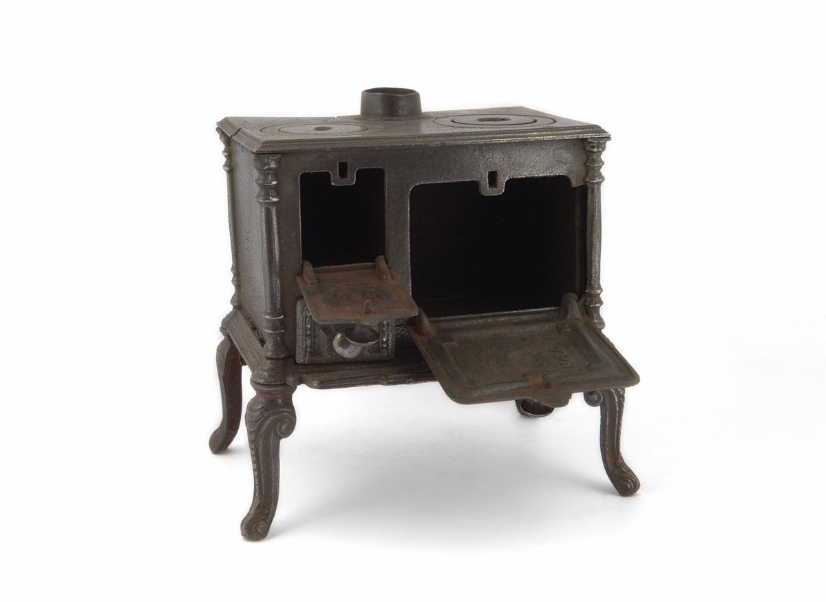 La photographie montre la cuisinière jouet de trois-quarts face avec portes ouve