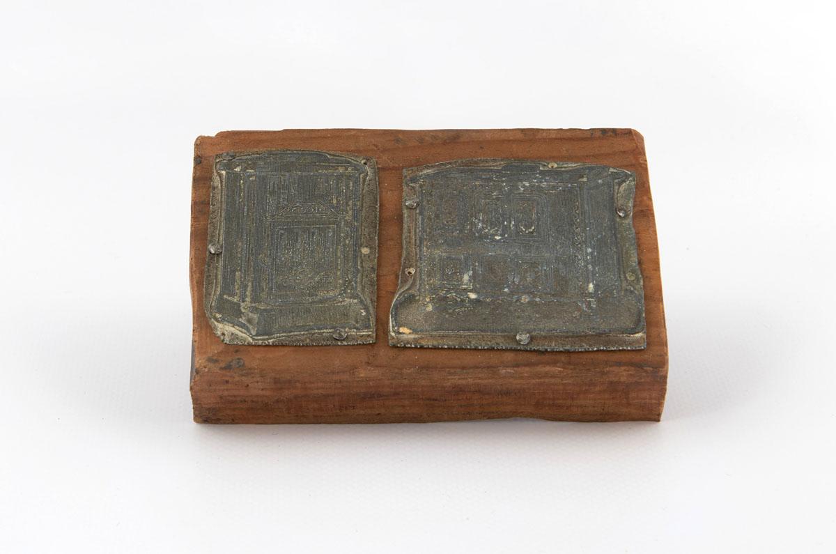 Vue de deux matrices de gravure en métal montées sur une planche en bois.