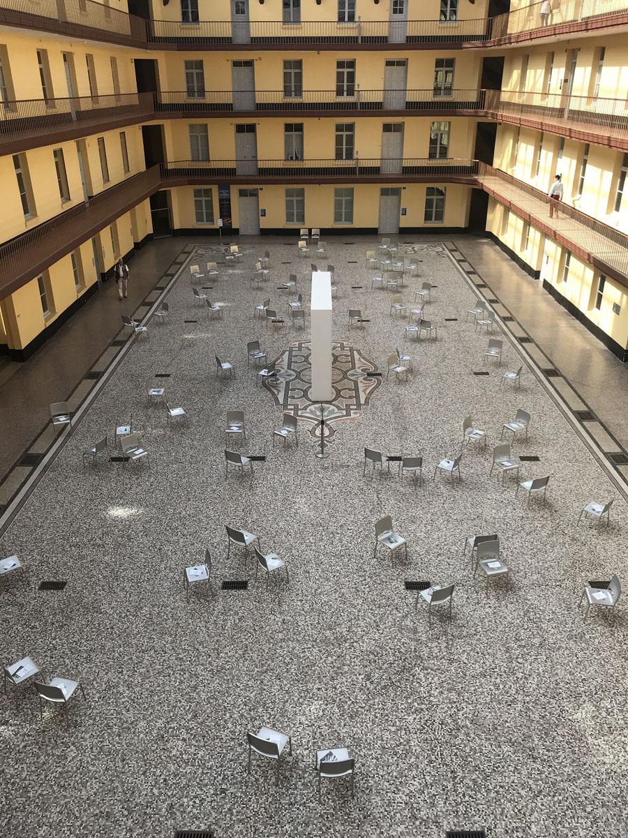 La photographie montre des chaises éparpillées dans la cour du pavillon central.