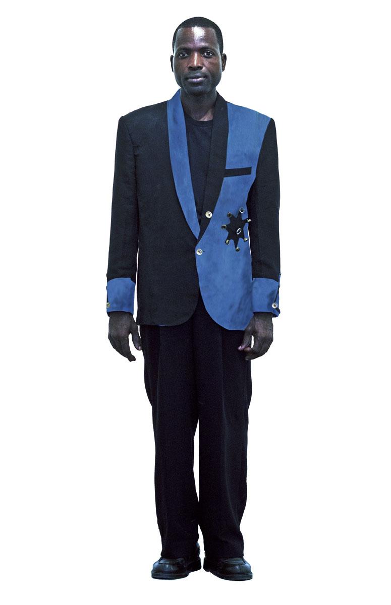 Portrait en pied de Pume Bylex dans un costume bleu et noir