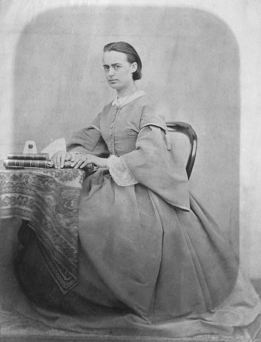 Portrait photographique de Marie Moret assise à une table