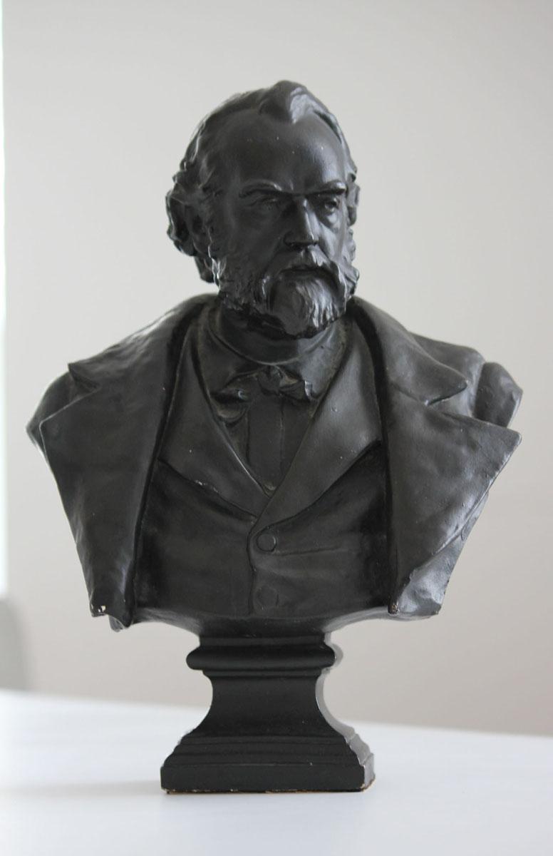 Vue de face du buste en plâtre teint à l'effigie de Godin
