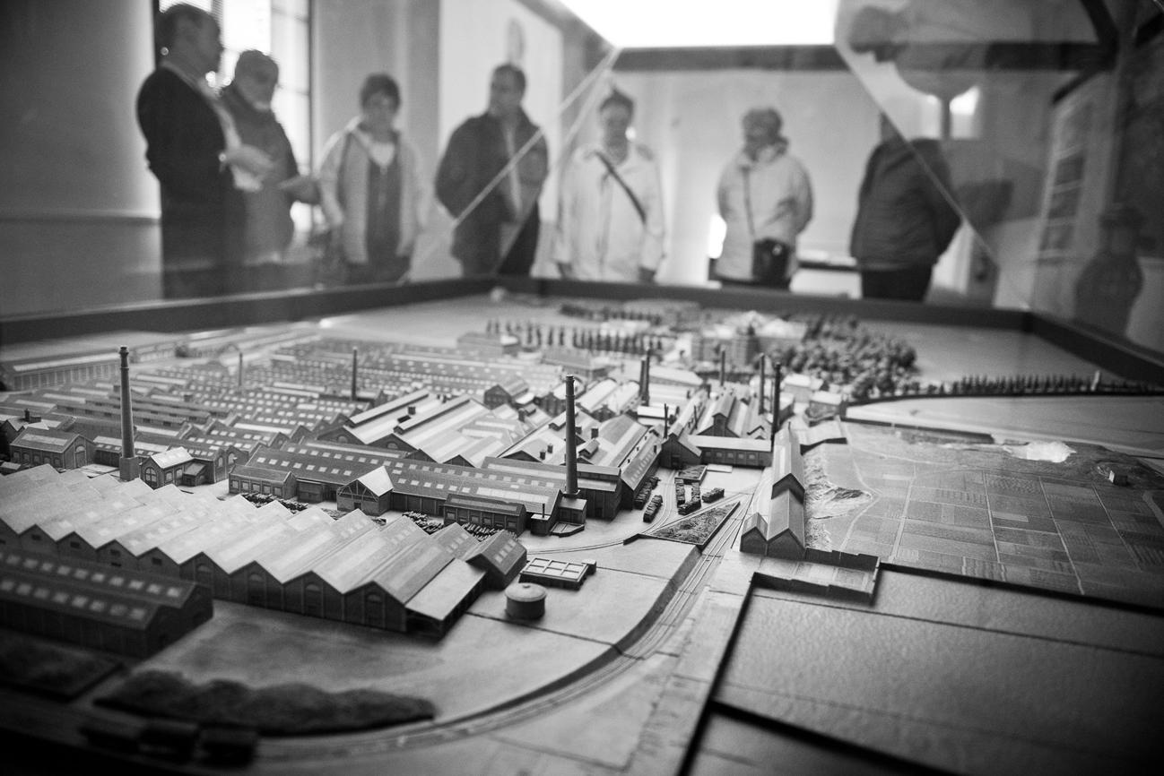 Des visiteurs sont autour du plan-relief du Familistère réalisé en 1931.