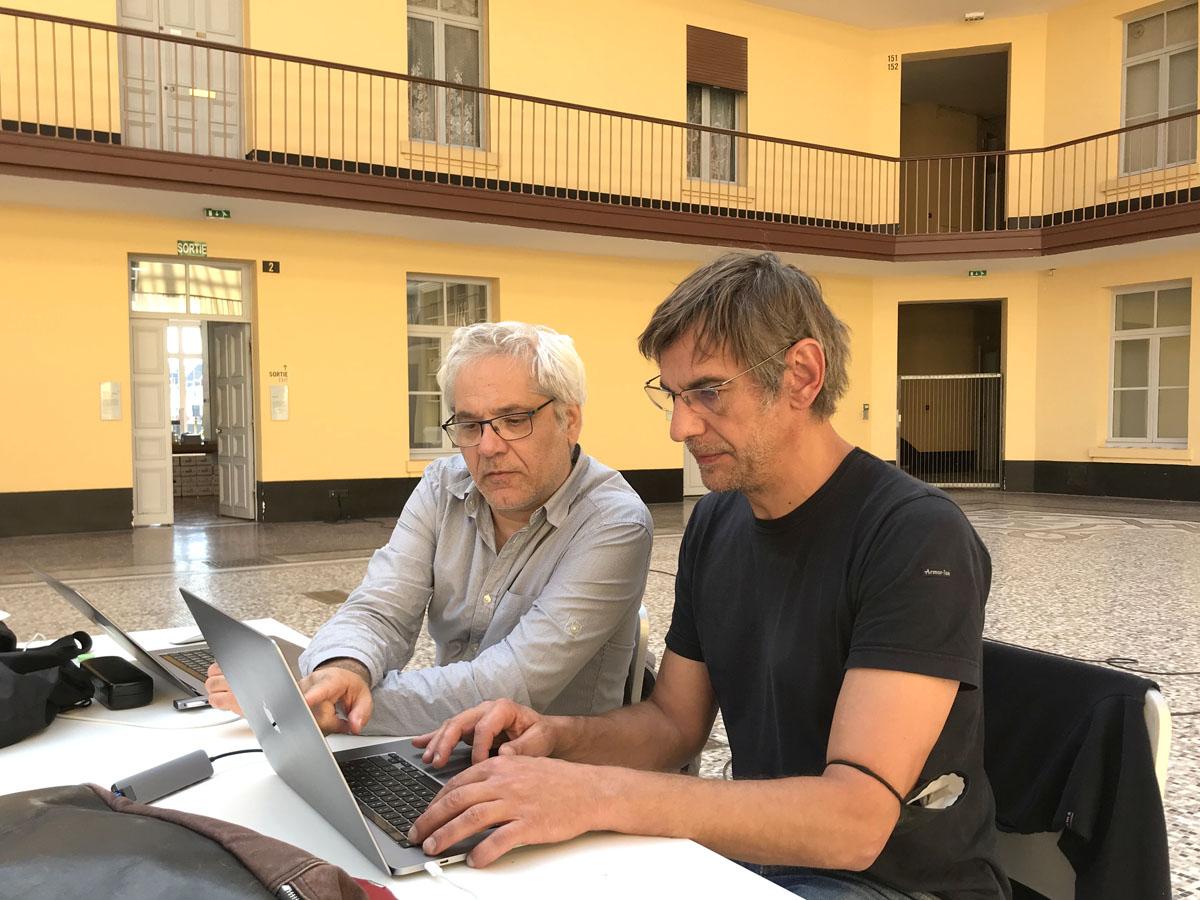 Vue de deux hommes assis à une table devant un ordinateur